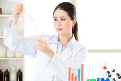 Travail soigneux et méticuleux de scientifique féminin asiatique images libres de droits