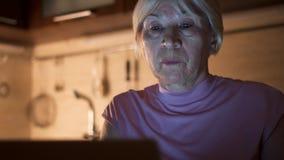 Travail supérieur de femme sur l'ordinateur portable du maison-bureau la nuit La femme d'affaires enlèvent des verres et des yeux banque de vidéos