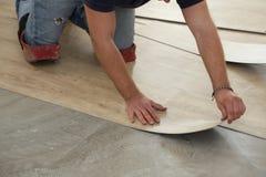Travail sur étendre le plancher Travailleur installant le nouveau plancher de tuiles de vinyle photographie stock