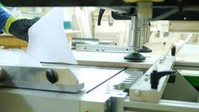 Travail sur la machine de forage moderne de travail du bois à une usine de meubles photographie stock libre de droits
