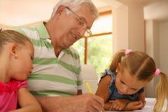 Travail travaillant de grand-père avec des petite-filles Photos stock