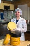 Travaillant à la production du fromage à la laiterie, avec des fromages photos libres de droits