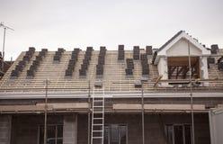 travaillant au recouvrement du toit et les tangons ou l'échelle d'un nouveau, deux histoire, immeuble commercial photos stock