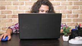 Travaillant sur un ordinateur portable, dactylographiant sur un clavier, adolescent moderne Un adolescent avec les cheveux bouclé banque de vidéos