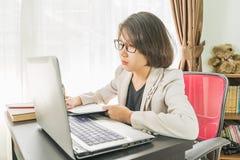 Travailler adolescent de femme sur l'ordinateur portable dans le siège social Images libres de droits