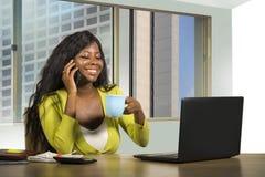 Travailler américain de femme d'affaires d'africain noir attirant sûr au bureau d'ordinateur parlant au téléphone portable satisf images stock