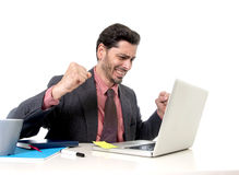 Travailler attrayant d'homme d'affaires heureux à l'ordinateur de bureau excité Photo stock