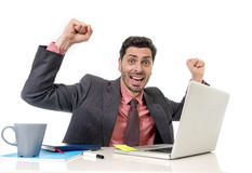 Travailler attrayant d'homme d'affaires heureux à l'ordinateur de bureau excité et euphorique Photo stock