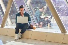 Travailler de attente de jeune étudiant masculin d'entrepreneur sur l'ordinateur portable dans le sunn Photos libres de droits