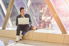 Travailler de attente de jeune étudiant masculin d'entrepreneur sur l'ordinateur portable dans le sunn Photographie stock