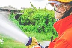 Travailler de sapeurs-pompiers de deux paires de mains tenant la poignée sur l'extrémité d'une eau de pompiers photo libre de droits