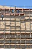 Travailler de travail au haut échafaudage dans le chantier de construction Photos libres de droits