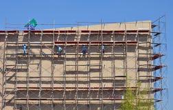 Travailler de travail au haut échafaudage dans le chantier de construction Image libre de droits