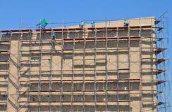 Travailler de travail au haut échafaudage dans le chantier de construction Photos stock