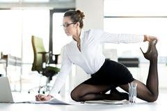 Travailler femelle flexible à la table au bureau photos stock