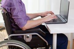 Travailler handicapé sur l'ordinateur portable photo libre de droits