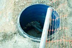 Travailler sur la nouvelle canalisation de trou d'homme d'eaux d'égout sur la rue Images libres de droits