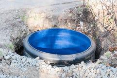 Travailler sur la nouvelle canalisation de trou d'homme d'eaux d'égout sur la rue Photos libres de droits