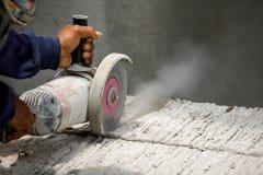 Travailleur à l'aide de l'outil pour couper le plancher en béton avec l'espace vide sur la droite Photographie stock libre de droits