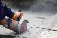 Travailleur à l'aide de l'outil pour couper le plancher en béton avec l'espace vide sur la droite Photo libre de droits