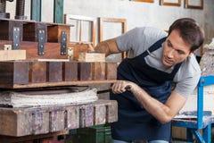 Travailleur à l'aide de la machine de papier de presse dans l'usine Image stock