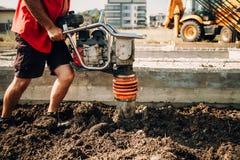 travailleur à l'aide du compacteur de sol sur le chantier de construction Base des détails de maison image stock