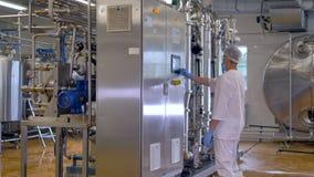Travailleur à l'atelier industriel actionnant l'équipement moderne d'usine 4K clips vidéos