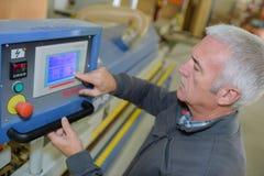 Travailleur à la machine-outil fonctionnante de presse de poinçon d'atelier par ordinateur images stock