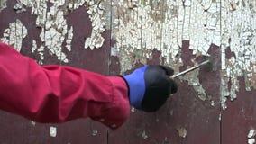 Travailleur éraflant la vieille peinture du mur en bois banque de vidéos
