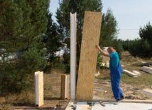 Travailleur érigeant des panneaux de mur sur un chantier photographie stock libre de droits