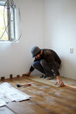 Travailleur étendant le parquet dans une chambre Photographie stock libre de droits