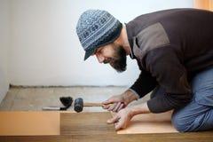 Travailleur étendant le parquet dans une chambre Image libre de droits