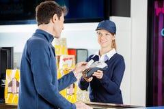 Travailleur acceptant le paiement de l'homme par NFC Photos stock