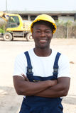 Travailleur africain debout avec les bras croisés au chantier de construction Photographie stock libre de droits