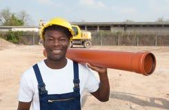 Travailleur africain riant avec le tuyau Photo stock