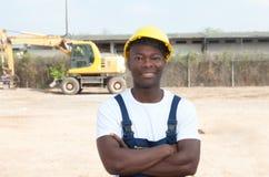 Travailleur africain riant avec les bras croisés au chantier de construction Image stock