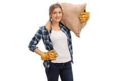 Travailleur agricole féminin portant un sac à toile de jute photographie stock