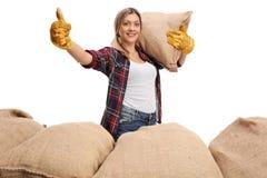 Travailleur agricole tenant le sac à toile de jute et renonçant au pouce Photographie stock