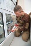 Travailleur appliquant la colle avec l'arme à feu de silicone photo stock