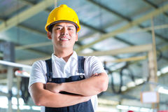 Travailleur asiatique dans une usine ou un ensemble industriel Photo libre de droits