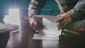 Travailleur assemblant la pièce en métal dans le manuel photo stock