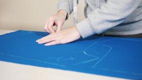 Travailleur aux croquis de repérage d'usine d'habillement sur le tissu bleu clips vidéos