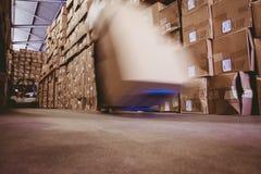 Travailleur avec l'empileur de camion de palette de fourchette dans l'entrepôt photos libres de droits