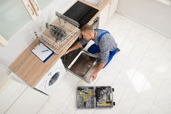 Travailleur avec la boîte à outils réparant le lave-vaisselle image stock