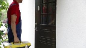 Travailleur avec la promenade de boîte à outils à une maison de client banque de vidéos