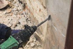 Travailleur avec le marteau électrique nettoyant le mur de briques rouge photo stock