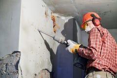 Travailleur avec le marteau de démolition cassant le mur intérieur photos libres de droits