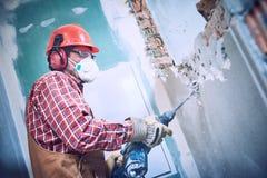 Travailleur avec le marteau de démolition cassant le mur intérieur image libre de droits