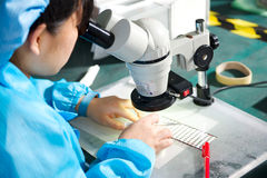 Travailleur chinois sur le microscope de contrôle d'usine photos libres de droits
