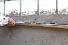 Travailleur concret de plâtrier au mur de la construction de maison Images libres de droits